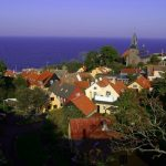 """<b>Gudhjem</b><br> Gudhjem – literally 'God's Home' – is a stunning fishing village of only 700 inhabitants on the northern shore of Bornholm, built into a steep cliff leading down to the harbour. It epitomizes what visitors love about the island: a sleepy village with tightly packed, colourful old houses, nestled between the Baltic Sea and Almindingen, one of the country's largest forests.  Photo: <a href=""""https://www.flickr.com/photos/ehrenbergkommunikation/"""">Ehrenberg Kommunikation/Flickr</a>"""